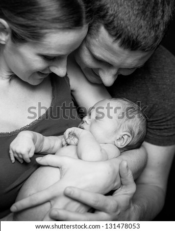 Beautiful mother and father smiling holding their newborn baby boy - stock photo