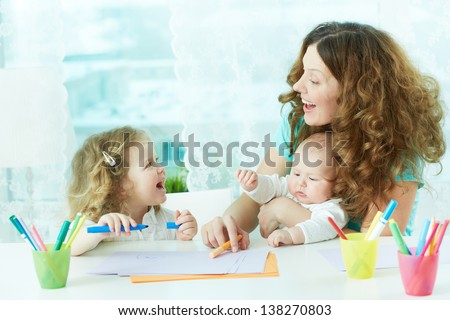 Beautiful mother and her children drawing at home - stock photo