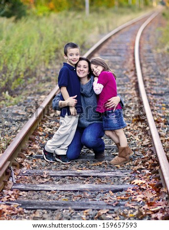 Beautiful mother and her children on train tracks - stock photo