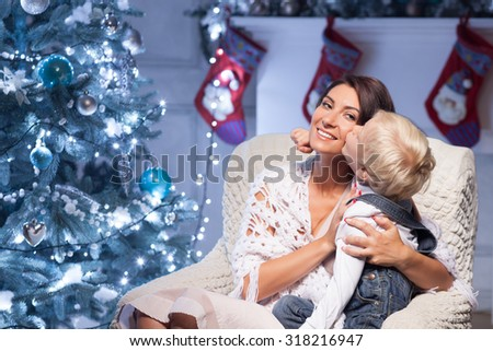Beautiful mother and her son are sitting on chair near New Year fir-tree. They are embracing. The boy is kissing his mother on her check with love. The lady is smiling happily - stock photo