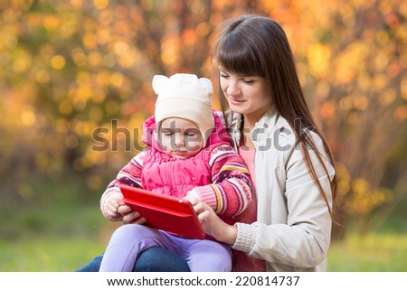 beautiful mother and kid girl playing at tablet pc outdoors in fall - stock photo