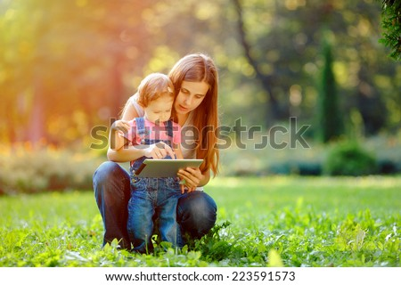 Beautiful mother and kid girl playing at tablet pc outdoors in fall. Happy mother showing her daughter funny pictures your tablet. Happy family, mother and daughter with tablet resting in the park. - stock photo