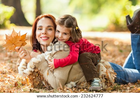 Beautiful mother and little daughter enjoying nice autumn day in a park - stock photo