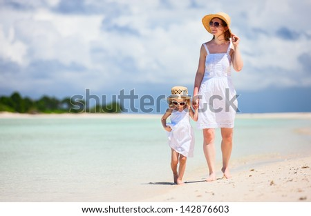 Beautiful mother and little daughter walking along tropical beach - stock photo