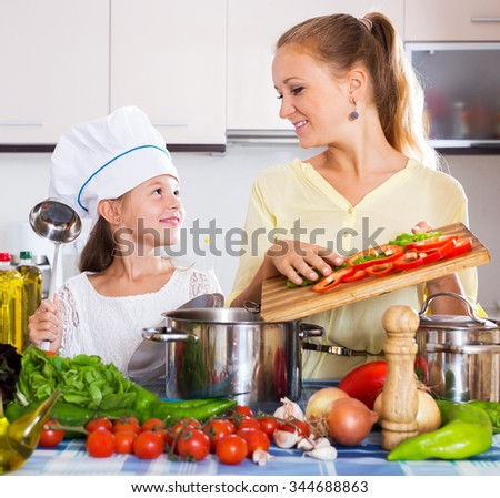 Beautiful mother and little girl preparing vegetables in slow-cooker - stock photo