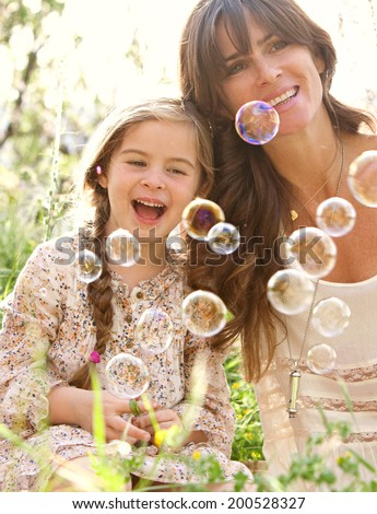 Beautiful mother and young daughter relaxing in a golden green field with trees, grass and flowers, playing to blow floating bubbles during a holiday vacation outdoors. Family activities lifestyle. - stock photo