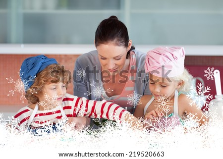 Beautiful mother helping their chilldren baking against snowflakes - stock photo