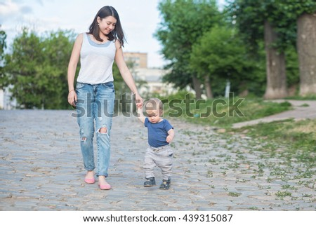 beautiful mother is walking on the old road with her little baby boy with first steps. One years old baby walking whith his mom outdoor - stock photo