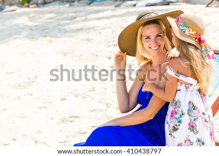 Beautiful mother lady in beach straw hat with her pretty blonde cute daughter. Woman in a beach chair smile to the camera. Girl say something to her ear. Happy family on the beach. Happy mothers day. - stock photo