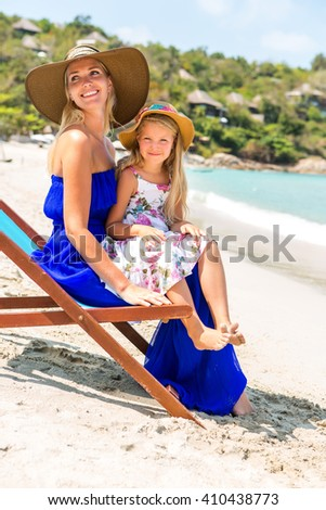 Beautiful mother lady in blue dress and beach straw hat with her pretty blonde cute daughter. Woman in a beach chair, little girl smile to the camera. Happy family on the beach. Happy mothers day. - stock photo