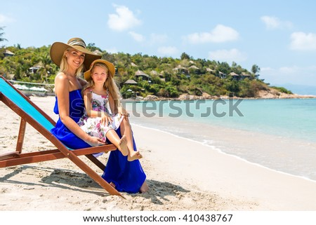 Beautiful mother lady with her pretty blonde cute daughter in dress and beach straw hat. Woman in a beach chair and little girl smile to the camera. Happy family on the shore. Happy mothers day. - stock photo