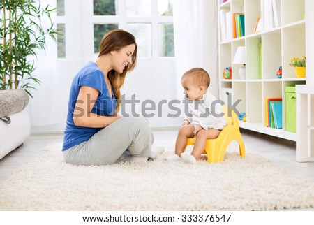 Beautiful mother learning little child how to sitting on potty at home - stock photo