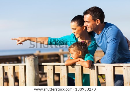 beautiful mother showing her family something at the beach - stock photo