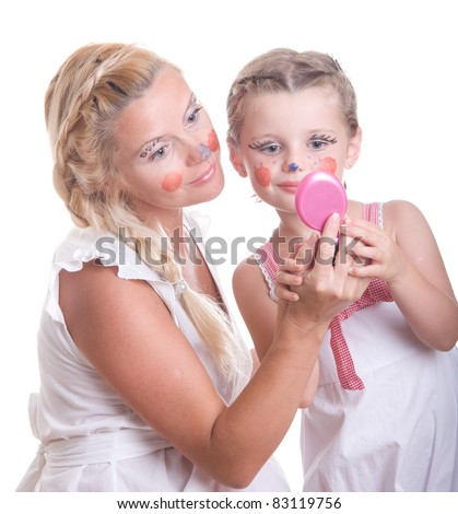 Beautiful mother with her daughter looking in the mirror at their creative face paint - stock photo