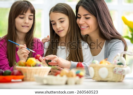 Beautiful mother with her daughters painting Easter eggs - stock photo