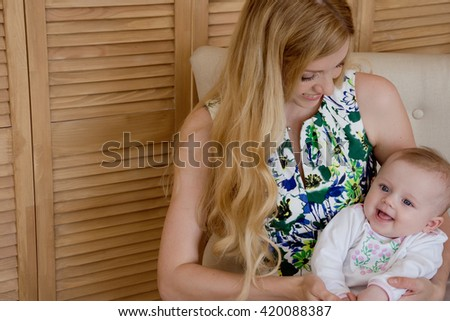 Beautiful mother with little daughter sitting on the couch at home.Parent and little kid relaxing at home. Family having fun together. - stock photo
