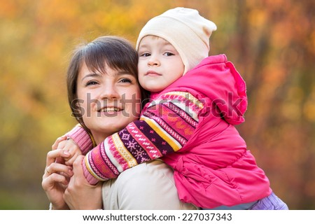 beautiful mother with toddler girl outdoor in fall - stock photo