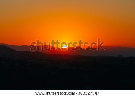 Beautiful Mountain And Sunset Over Mijas, Spain. Dark Silhouette of Mountains on Yellow Sunrise Background - stock photo