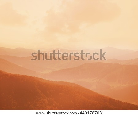 Beautiful mountain landscape. Mountains and hills in the haze before sunset. - stock photo