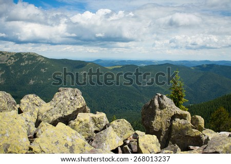 Beautiful mountain landscape. Mountains are visible to the horizon. Cloudy sky.   - stock photo
