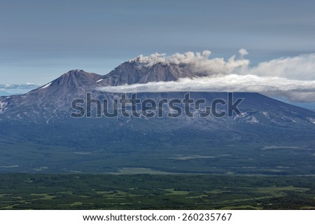 Beautiful mountain landscape of Kamchatka Peninsula: eruption active Zhupanovsky Volcano in explosion of magmatic gases, accompanied by release of crater of volcano of large masses of steam and ashes - stock photo