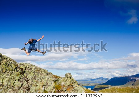 Beautiful mountain landscape with sportive jumping man - stock photo