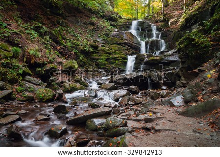 Beautiful mountain waterfall in the autumn forest - stock photo