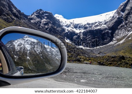 Beautiful mountains seen on the rearview mirror. Road to Milford Sound in New Zealand  - stock photo
