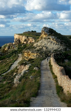 Beautiful mountains view with nice cloudy sky on sunny summer day in Malta, road to the rock with blue sky background, maltese landscape, maltese nature, hiking in mountains in Malta, Dingli cliffs  - stock photo