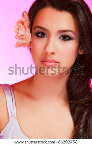 Beautiful multicultural young woman in a beauty studio portrait pose with a purple background. - stock photo