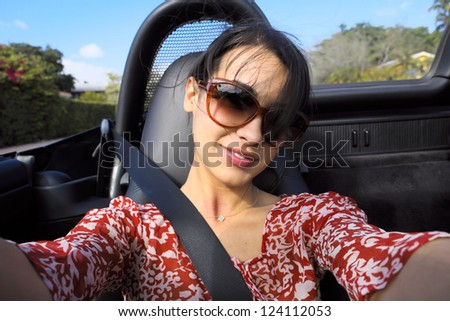 Beautiful multicultural young woman outdoor portrait in a convertible automobile. - stock photo