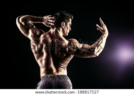 Beautiful muscular man bodybuilder posing back over dark background. - stock photo