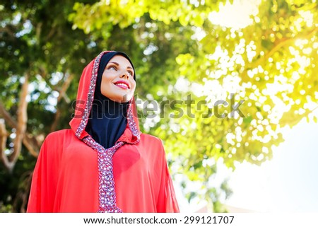 beautiful muslim caucasian woman wearing red dress and hijab in the park - stock photo