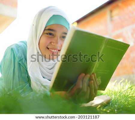 Beautiful Muslim girl reading book with hijab and smiling - stock photo