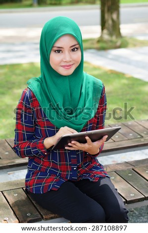 Beautiful muslim girl with her tablet in a park  - stock photo