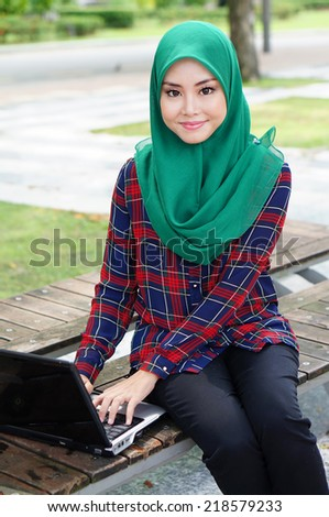beautiful muslim girl with laptop at the park - stock photo