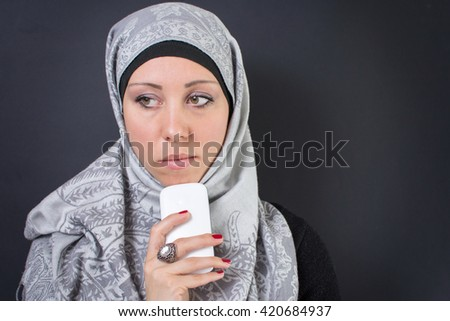 Beautiful muslim woman in hijab holding a mobile phone - stock photo