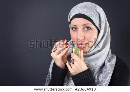 Beautiful muslim woman in hijab with a perfume - stock photo