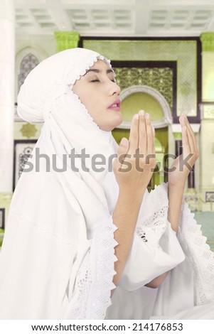 Beautiful muslim woman praying inside mosque - stock photo