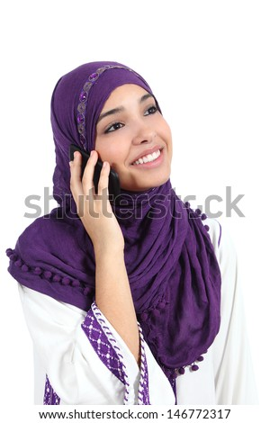 Beautiful muslim woman wearing a djellaba talking on the mobile phone isolated on a white background                - stock photo