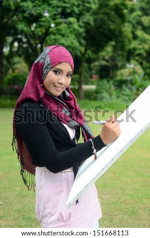 Beautiful muslim woman wearing scarf with white paper painting - stock photo