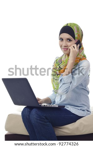 Beautiful muslim woman with computer and make a phone call isolated on white background - stock photo