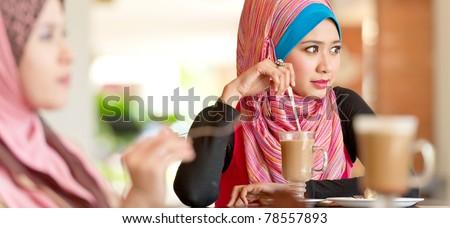 Beautiful Muslim women having lunch at coffee shop - stock photo