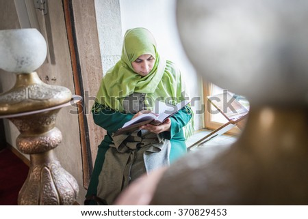 Beautiful Muslim young woman inside the mosque reading holy book Koran - stock photo