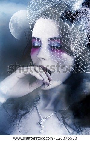 Beautiful Mysterious Female Vampire Standing In A Haunted Foggy Field Against Blue Sky Full Moon - stock photo