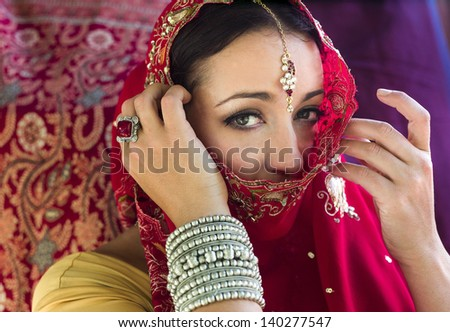Beautiful, mysterious woman in red Indian sari with traditional jewelry, face partially covered. Horizontal format. Red sari with red brocade background. - stock photo