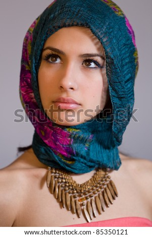 Beautiful mysterious young multicultural woman wearing a purple shawl. - stock photo