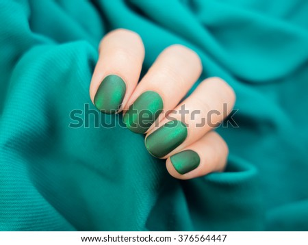 Beautiful nail polish in hand, close-up, green nail art manicure - stock photo