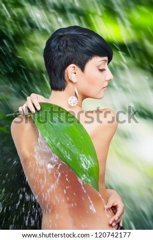 Beautiful naked back of young woman closing by palm leaf off splash of water against wet green background - stock photo