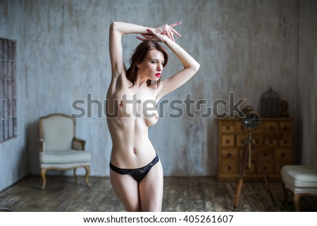 Beautiful naked body of young and sexy woman. Sexy woman topless model posing in a studio. - stock photo